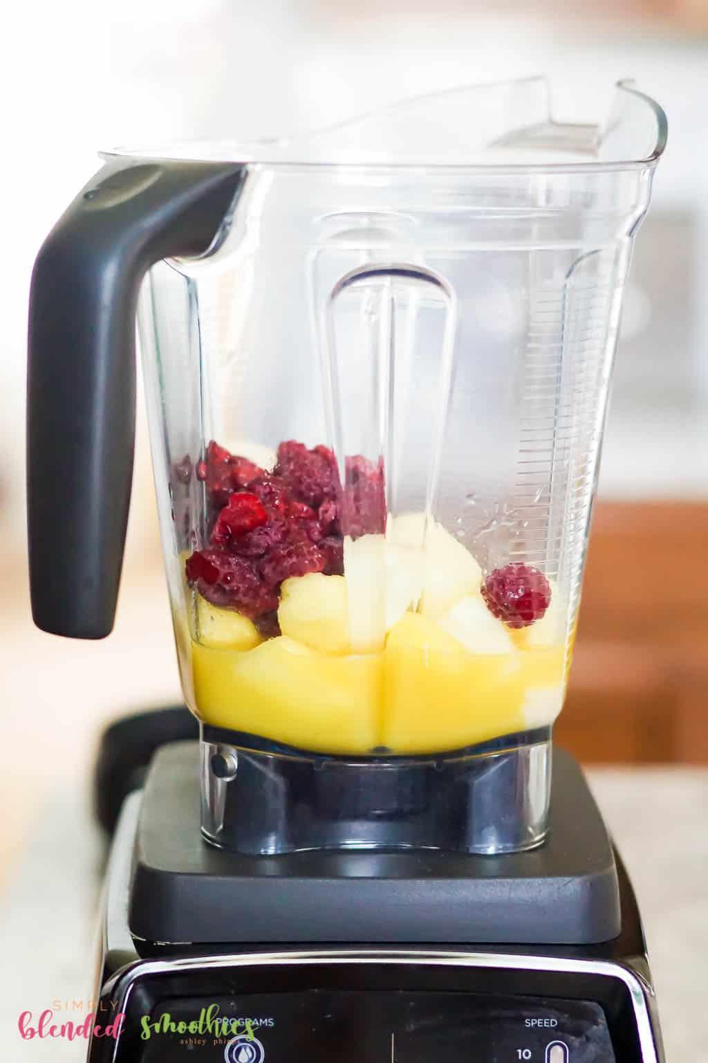 Pineapple Raspberry Smoothie ingredients in a blender
