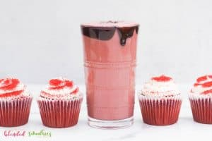 red velvet shake with chocolate syrup dripping down the side chocolate flakes and red velvet cupcakes on the side