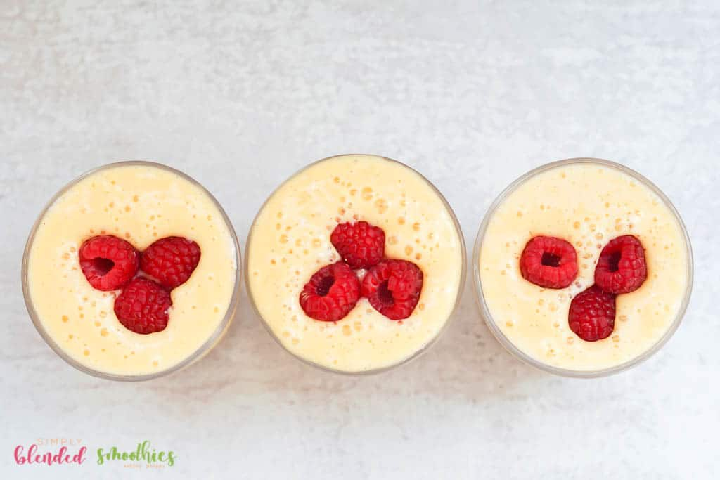 raspberries on top of a smoothie made with peaches