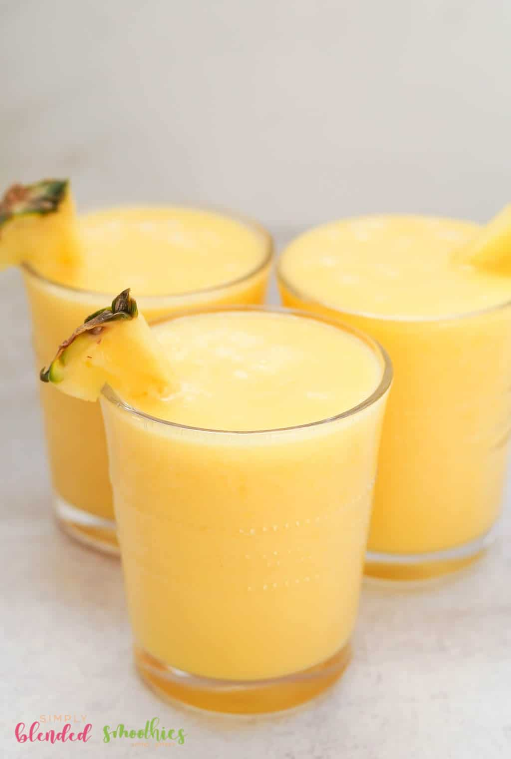 smoothie made with peaches and pineapple in clear glasses with pineapple garnish