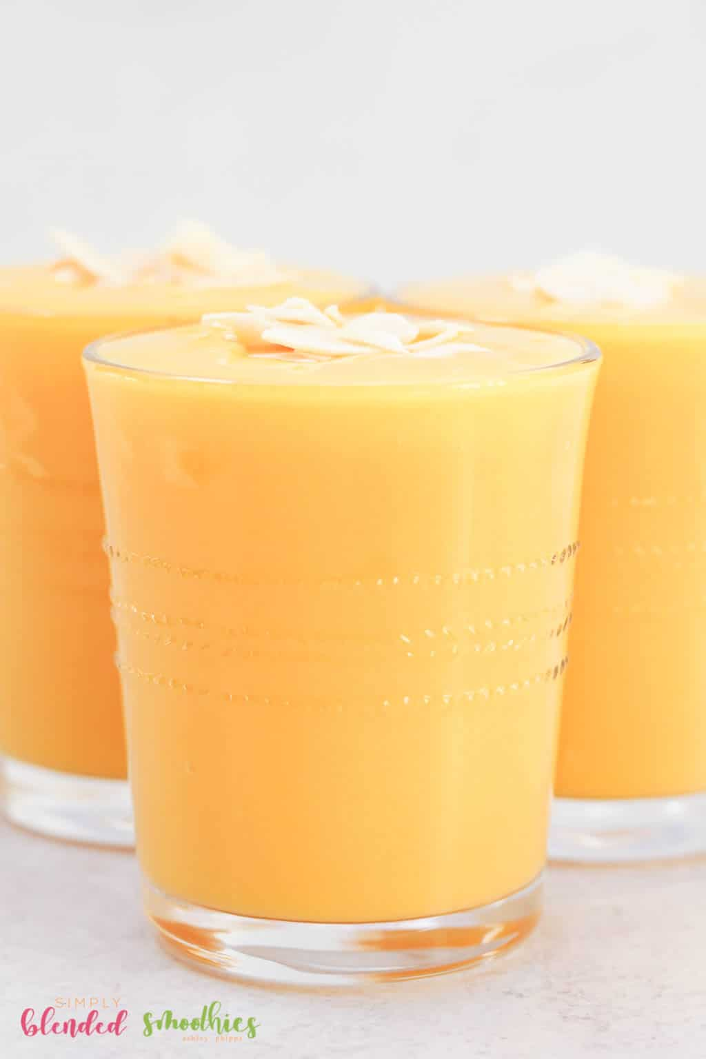 Close up vertical photo of mango peach smoothie in a clean glass with coconut flakes on top